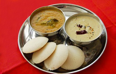 Idli with dishes of Sambar and Coconut Chutney